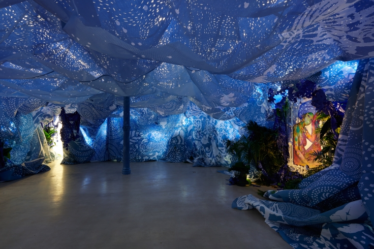 Installation including two paintings, blue wall and ceiling hangings, tropical foliage