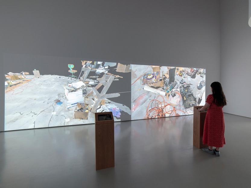 a woman stands at one of two pedestals in a gallery in front of two large-scale projections showing an artist's messy studio