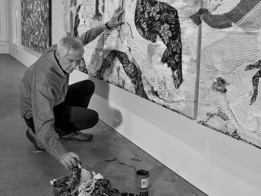 black and white portrait of Peter Sacks working on a large painting in his studio