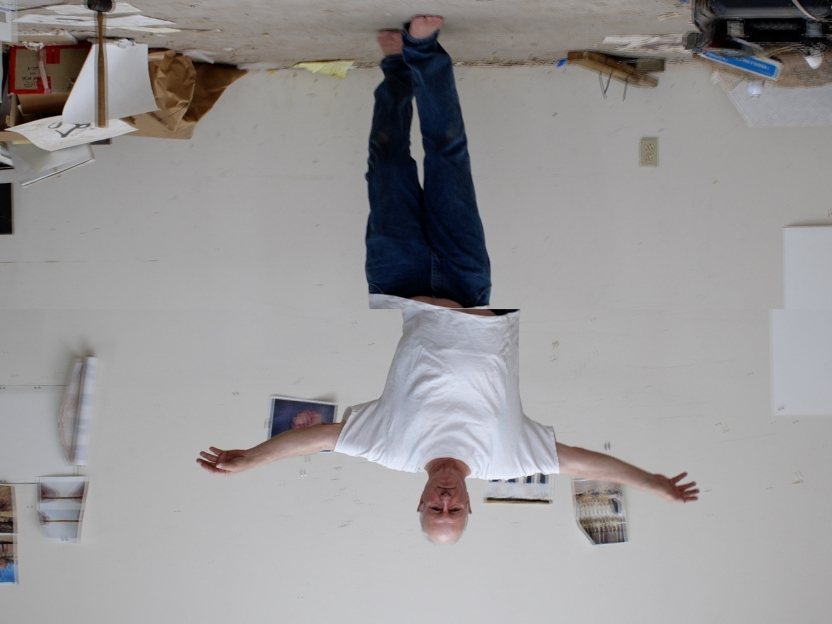 upside down image of a man in a tee shirt and jeans walking with his arms outstretched to the side