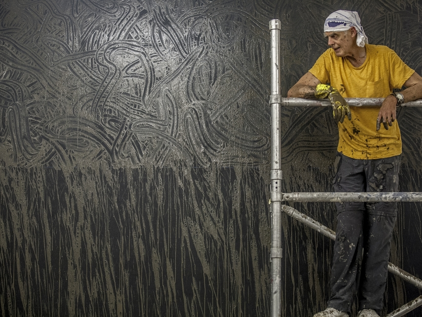 Richard Long standing on scaffolding in front of a mud artwork on the wall