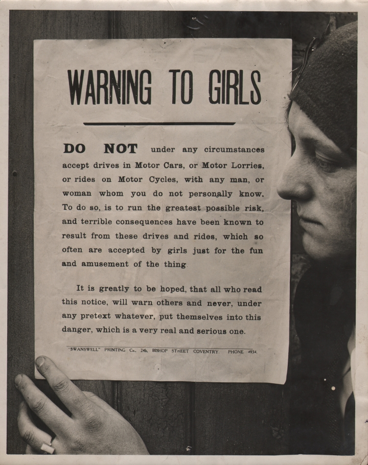 """General Picture News, Churches Warning to Girls, c. 1920. A woman in profile on the right of the frame with one hand on a pasted sign that begins: """"Warning to girls: Do not under any circumstances accept drives in Motor Cars, or Motor Lorries, or rides on Motor Cycles, with any man, or woman whom you do not personally know..."""""""