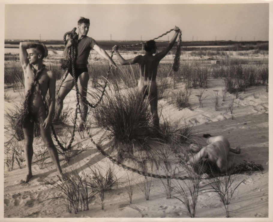 PaJaMa, Glenway Wescott, George Platt Lynes, Paul Cadmus, [unidentified], ​c. 1941. Four men on the beach with a thick rope connecting them. Three are standing (left), one lays facedown in the sand.