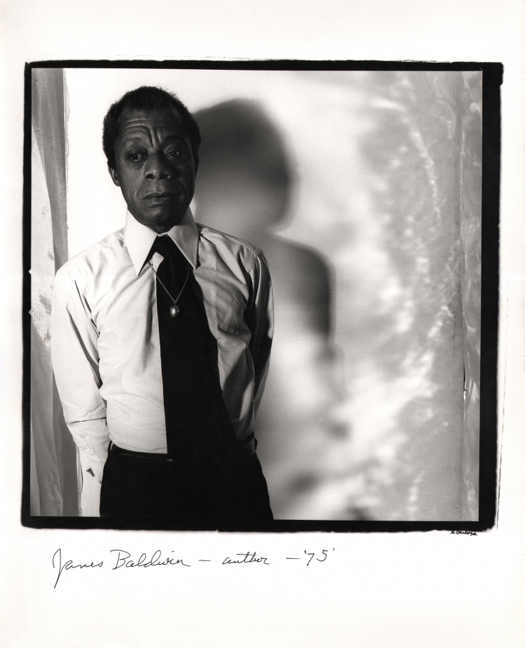 Anthony Barboza, James Baldwin - Author, 1975. Subject stands to the left of square frame with his shadow cast to the right onto the backdrop.