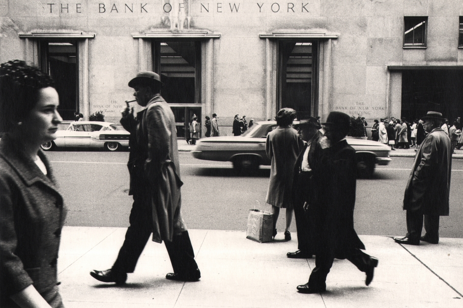Simpson Kalisher, Untitled, c. 1959. Pedestrians walk horizontally across the frame on a sidewalk across the street from the Bank of New York, seen in the background.