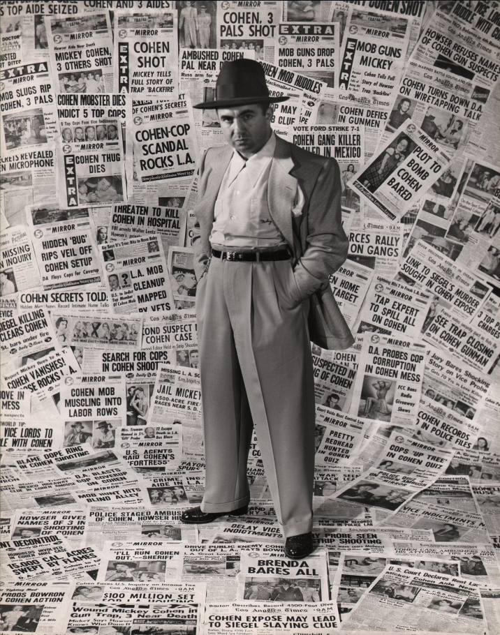 Ed Clark, Mickey Cohen, Gangster, 1949. A suited man stands against a backdrop of newspapers pasted to the wall and ceiling, hands in pockets, looking to the camera with a serious expression.