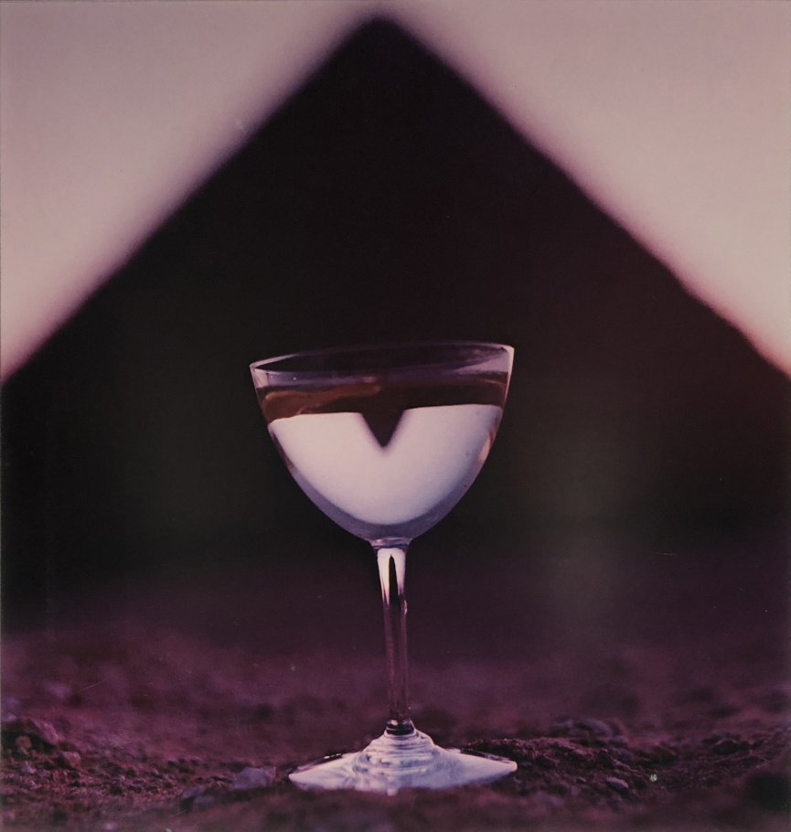 Bert Stern, Martini & Pyramid, for Smirnoff Vodka, 1955. Martini glass on sand with a triangle shape out of focus in the background.