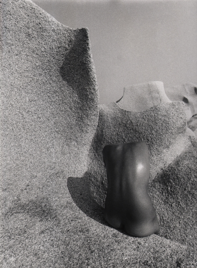 Pino Dal Gal, Capo Testa (Sardinia), 1977. Abstracted nude torso photographed from behind against a stone landscape.