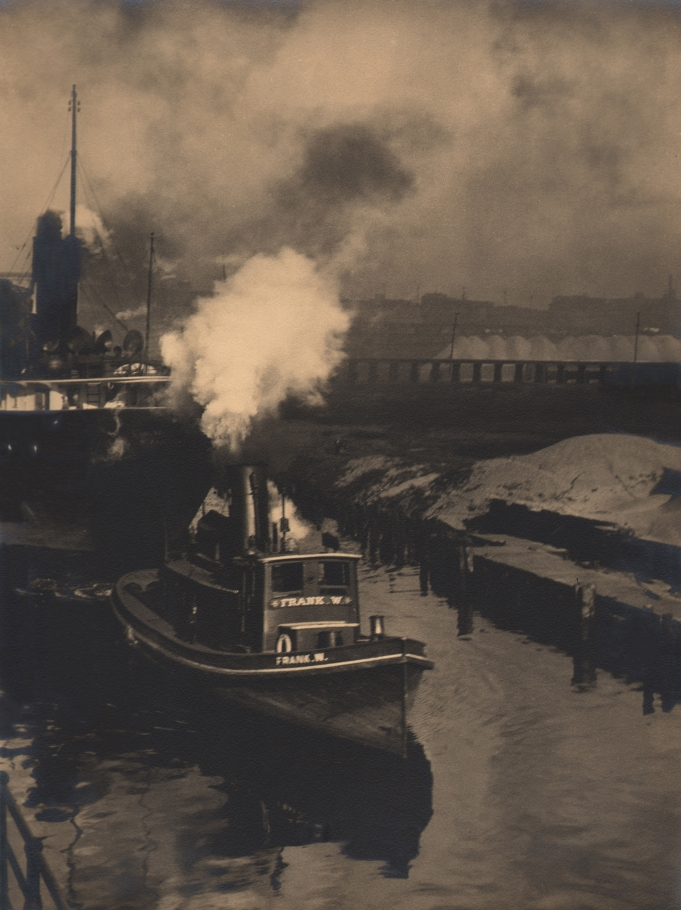 """Margaret Bourke-White, 'Frank W.' on the Cuyahoga, c. 1929. Small steam ship marked """"Frank W."""" in the water near a dock."""