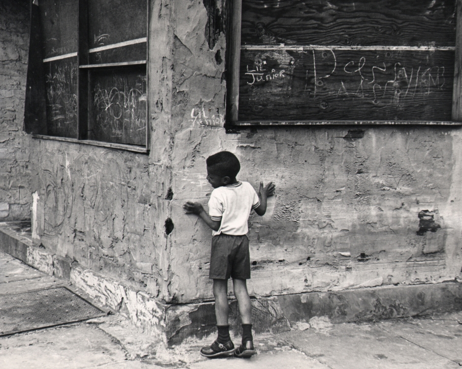 20. Beuford Smith, Playing 'Hide and Seek,' 1968. A young boy stands against the corner of a run-down building.