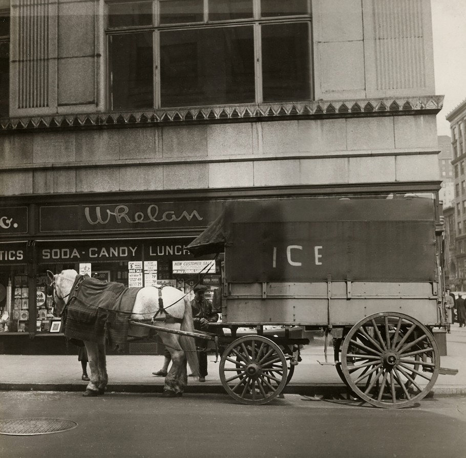 """Cecil Beaton, New York, c. 1935. A horse-drawn carriage marked """"Ice"""" on the street in front of a building marked """"Whelan Soda Candy Lunch"""""""