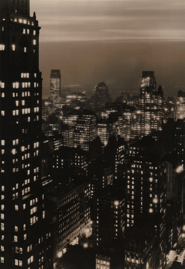 Paul J. Woolf, New York Skyline at Dusk, c. 1935. Night time cityscape with overcast sky and one building filling the left quarter of the vertical frame.