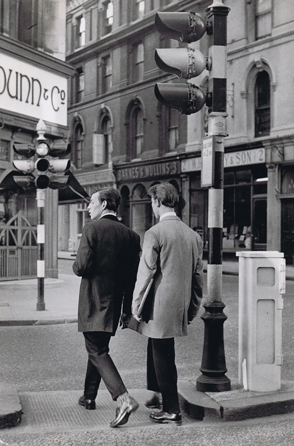 Henri Cartier-Bresson, Teddy Boys on Oxford Street, c. 1955. Two men, back to the camera, walk across a city street, passing a traffic light on the right.