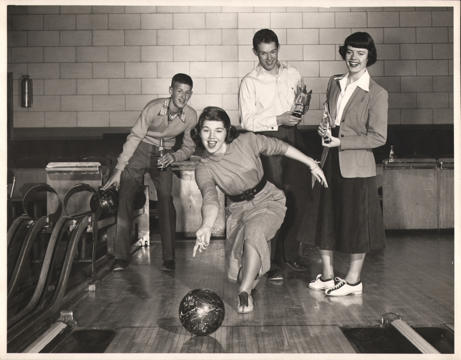 Ralph Bartholomew, Pepsi-Cola, 1950. A teenager bowling while three other teens look on from behind holding glass bottles of Pepsi.