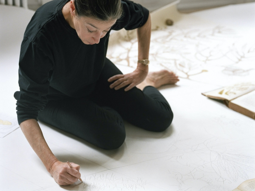 Color photograph of Michele Oka Doner drawing on the floor