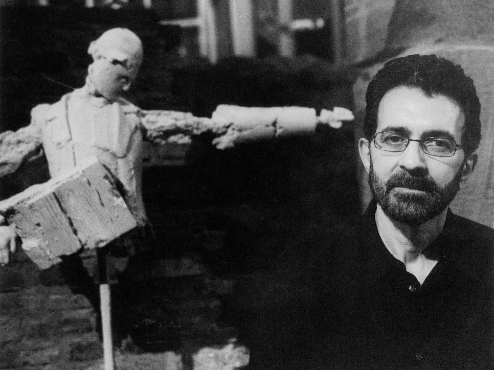 Black and white photographic portrait of Grisha Bruskin and a figurative sculpture