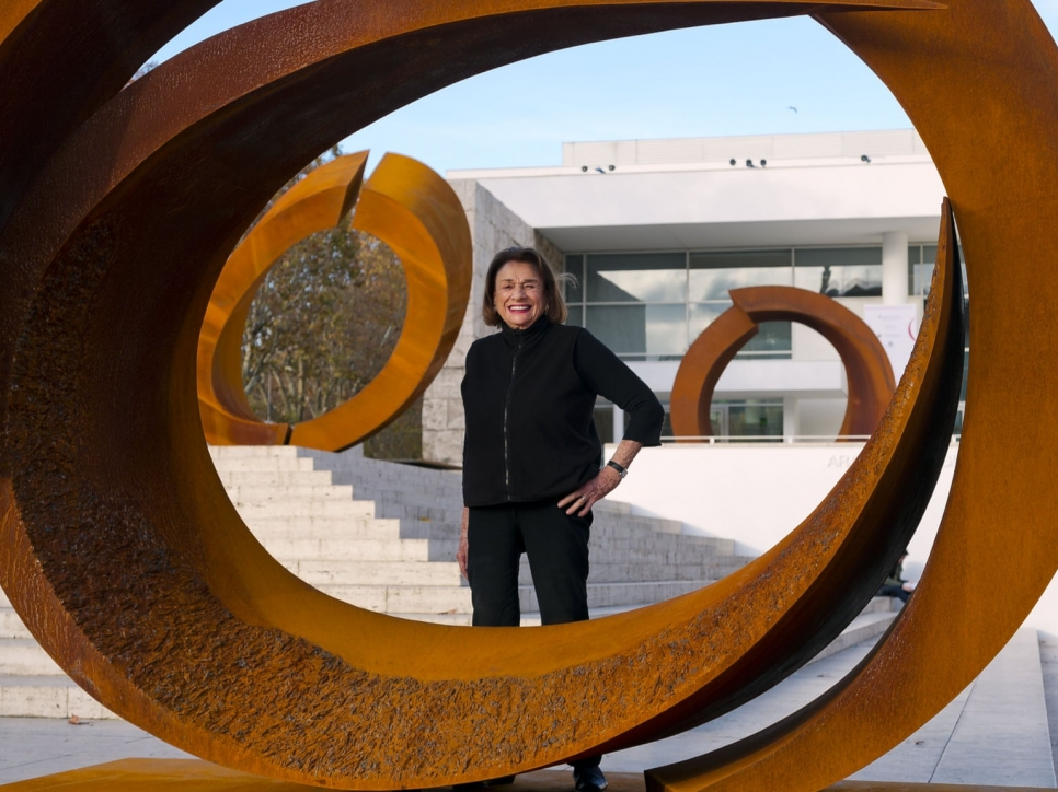 Color photographic portrait of Beverly Pepper with sculptures made with cor-ten steel from the curvae series