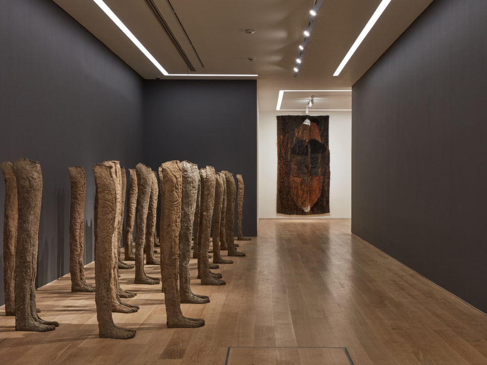 Installation view of burlap and resin sculptures and a textile work by Magdalena Abakanowicz