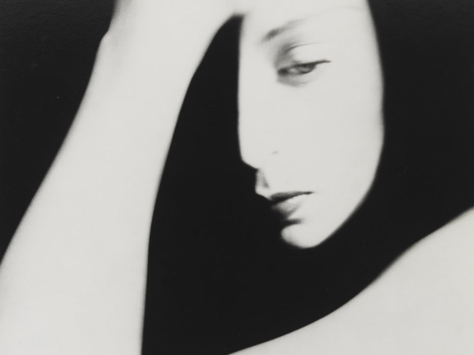 Black and white photographic by Bill Brandt featuring a shadowed close-up view of half of a woman's face and her hand resting on her forehead