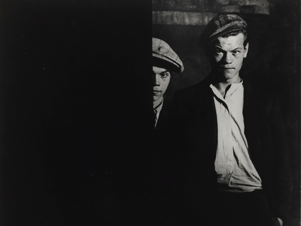 Black and white photographic by Brassaï featuring two men wearing hats. Half of one man's face is showing behind a barrier, and the other's full face is showing