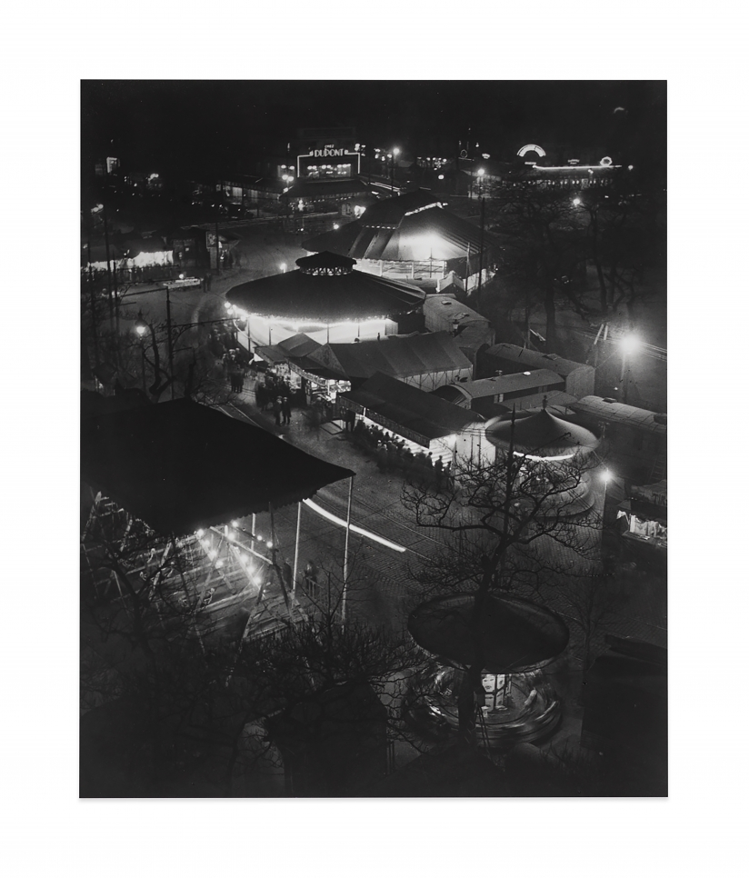 Black and white photographic by Brassaï featuring a birds-eye-view of a carnival scene