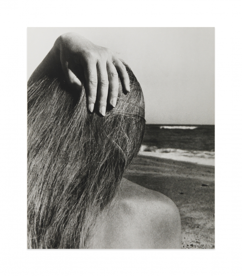 Black and white photograph by Bill Brandt showing the back of the head of a female figure on the beach