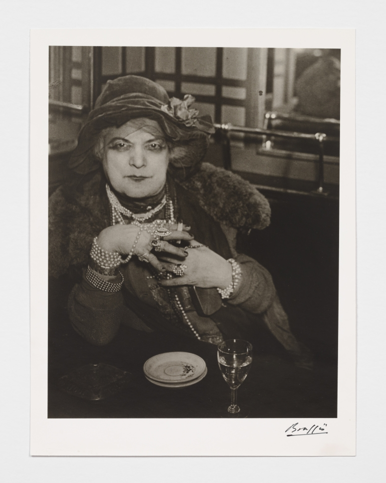 Black and white photographic by Brassaï featuring a woman dressed in jewelry and wearing a hat looking at the camera