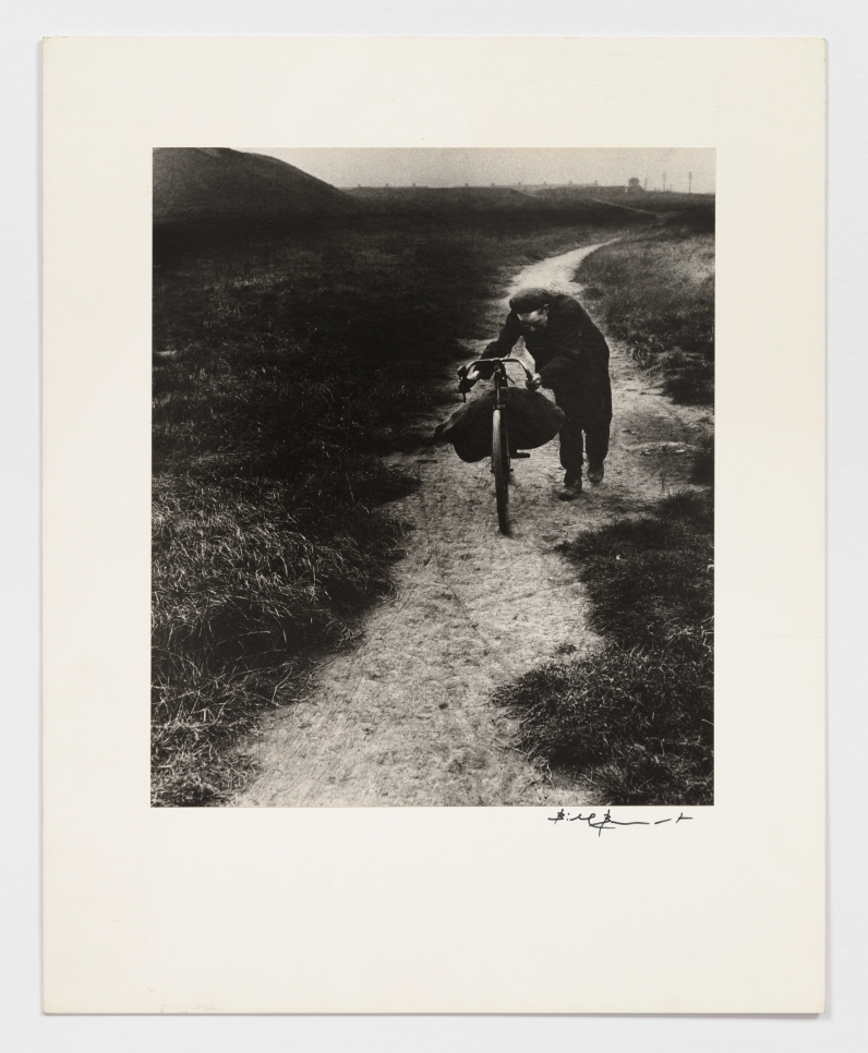 Black and white photographic by Bill Brandt featuring a man walking down a sand path with a bike