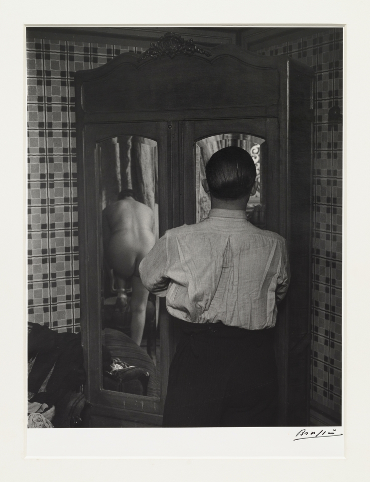 Black and white photographic by Brassaï featuring the behind view of a man looking at the reflection of a woman changing through a mirror