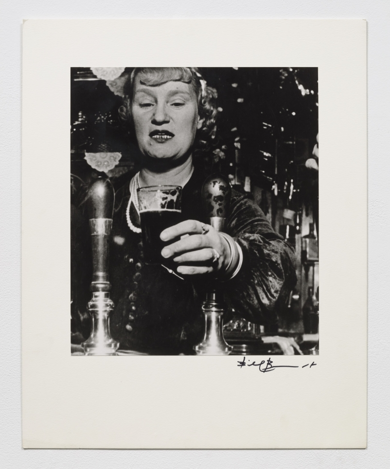 Black and white photographic by Bill Brandt featuring a woman serving a cocktail