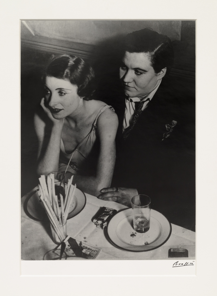 Black and white photographic by Brassaï featuring a couple sitting at a dinner table