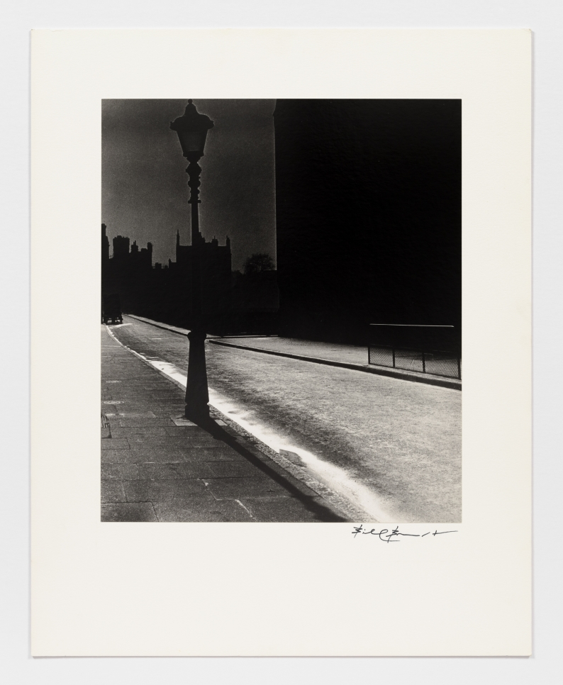 Black and white photographic by Bill Brandt featuring an empty street at night and the silhouette of a street lamp