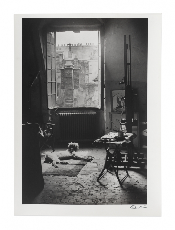 Black and white photographic by Brassaï featuring a dog laying down under a window in an art studio