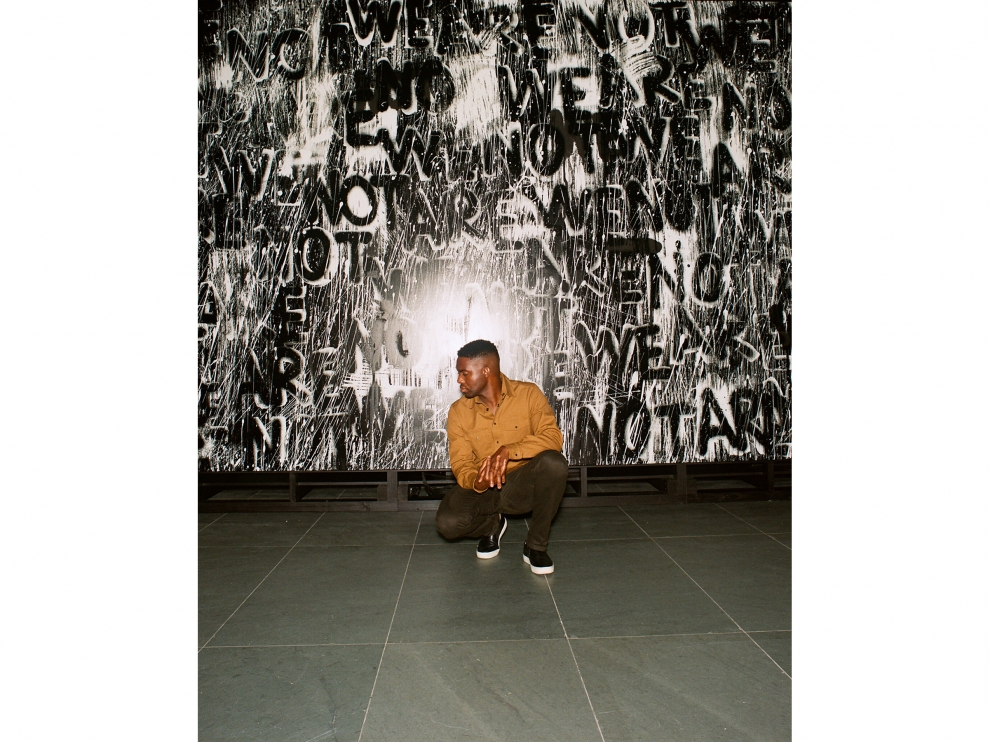 Photograph of Adam Pendleton crouching in front of one of his silkscreen artworks