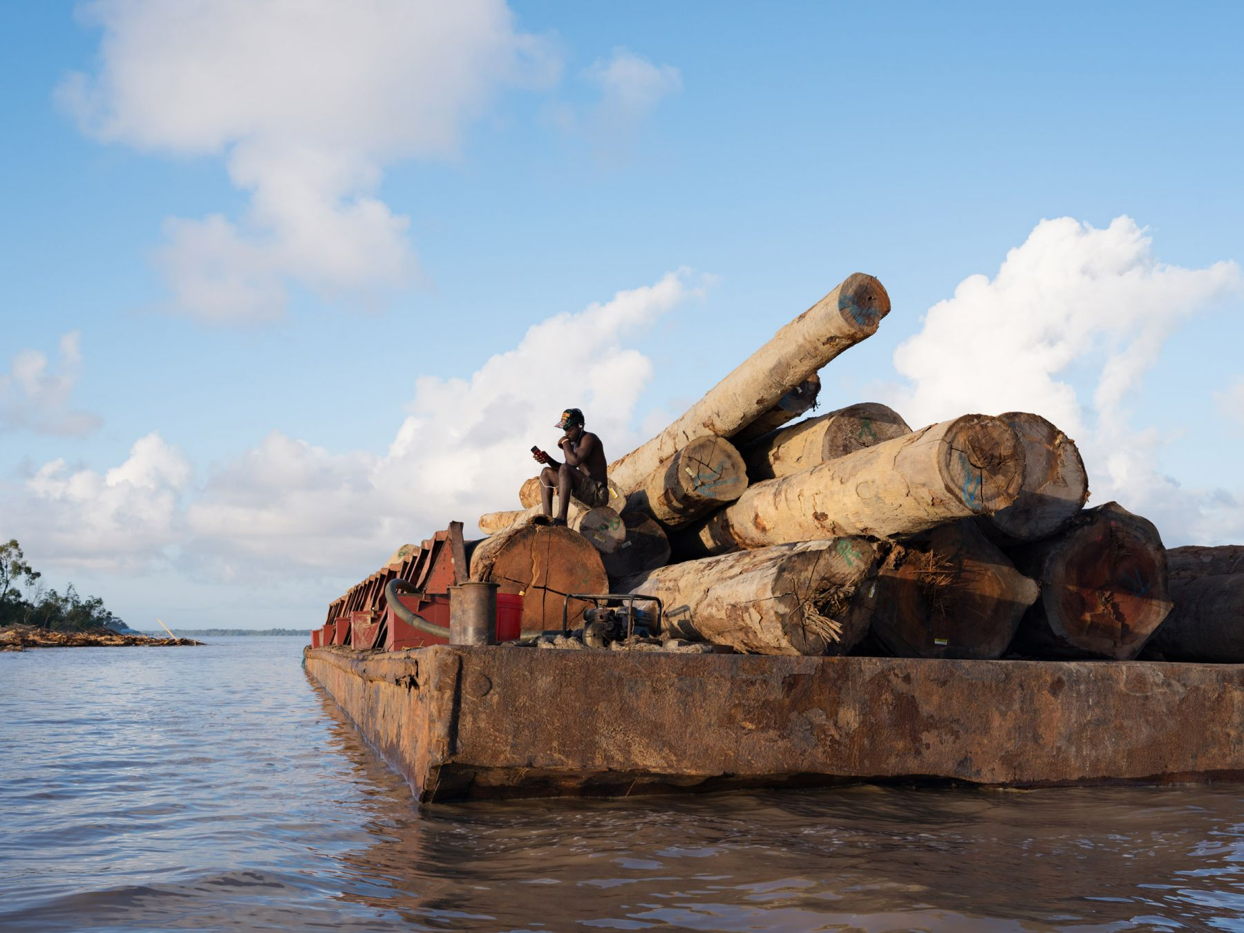 LUCAS FOGLIAKurt Guarding Logs for Export to China, Essequibo River, Guyana, 2016, Pigment Print34 x 44 inchesEdition of 8