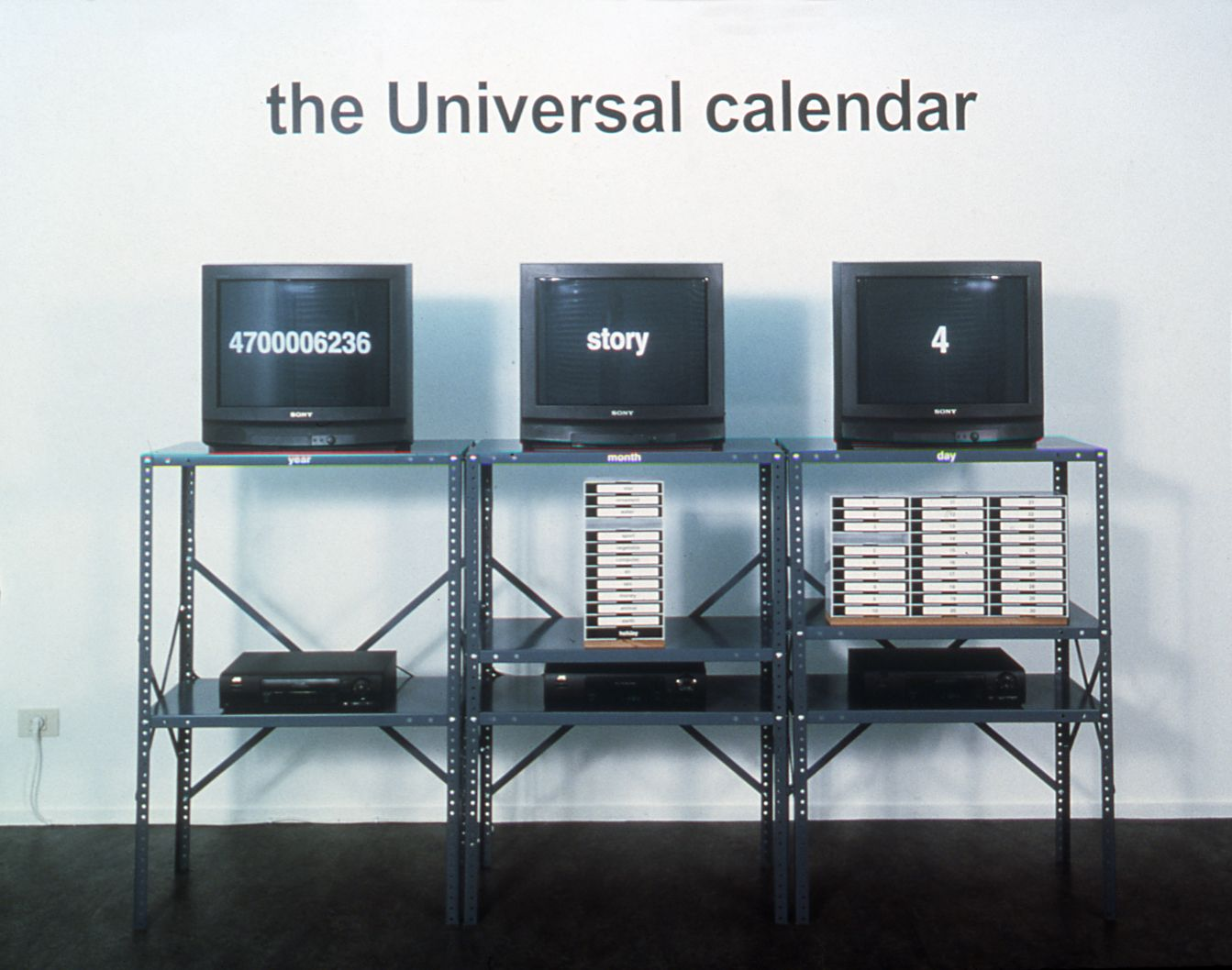 Jonathan Horowitz, The Universal Calendar, 1999, 43 continuous vhs tapes, industrial stand, wall text