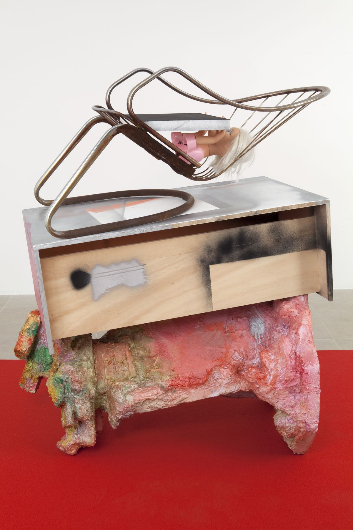 Rachel Harrison, The Spoon Bender, 2011, wood, polystyrene, cement, acrylic, felt, canvas, steel chair, plastic doll, and eyeglasses, 53 1/2 x 59 x 77 inches overall