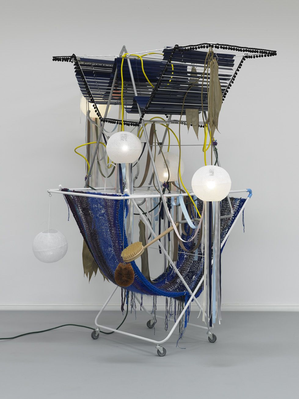 Haegue Yang  Dilemma Circus, 2010  2 drying racks on casters, light bulbs (frosted), lamp shades, cable, ribbon, aluminum venetian blinds, knitting yarn, dried lotus leaves, cosmetic sponge, metal ring, metal chain, body brush  57 1/8 x 49 1/4 x 72 3/4 inches (145 x 125 x 185 cm)