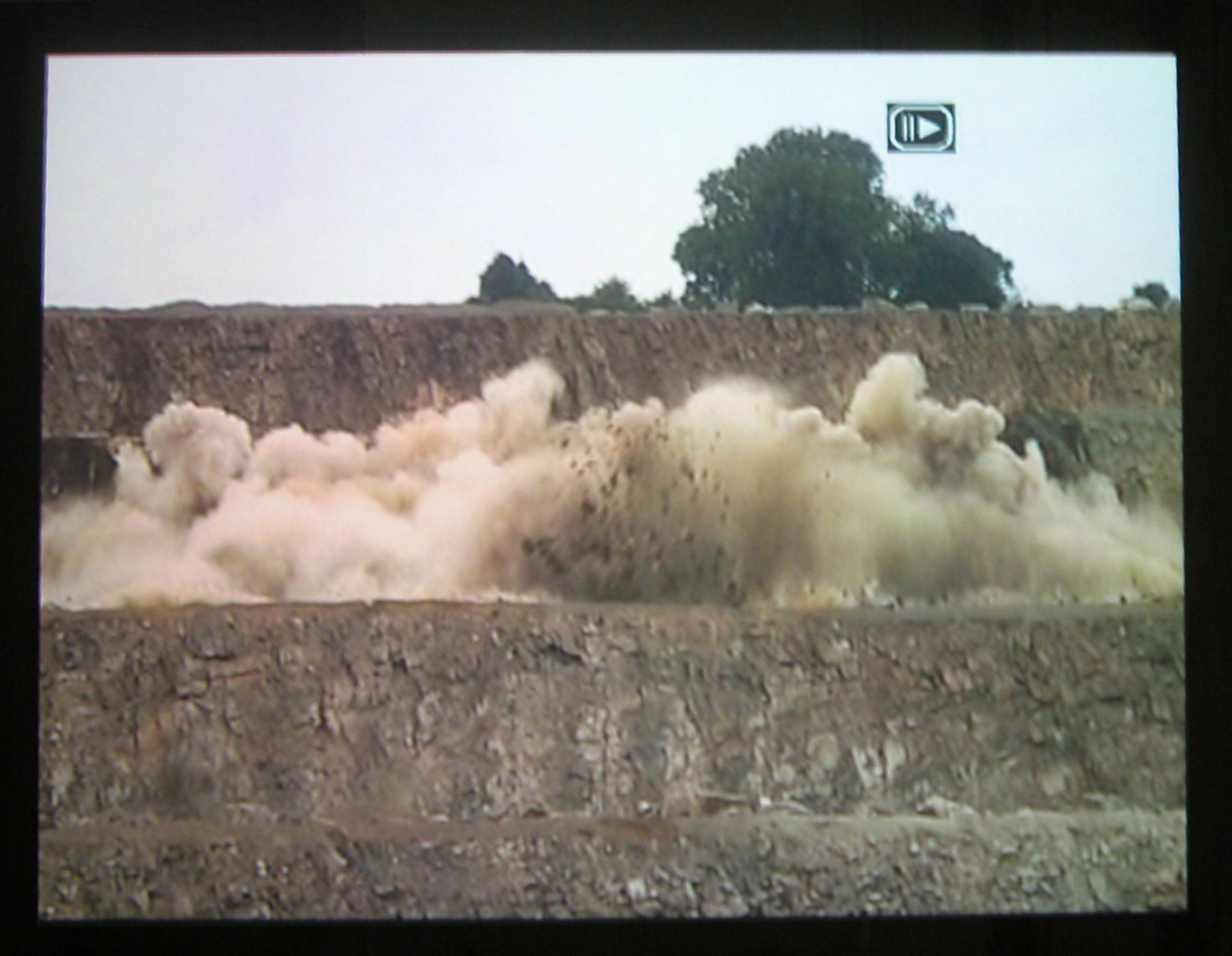 """Quarry, 2003 (still),  Two Parts: """"Blast"""" (4 minutes), """"Dr. Chris Alabaster"""" (12 minutes),  2 DVDs, bleachers, wooden screen,  Installation dimensions variable"""