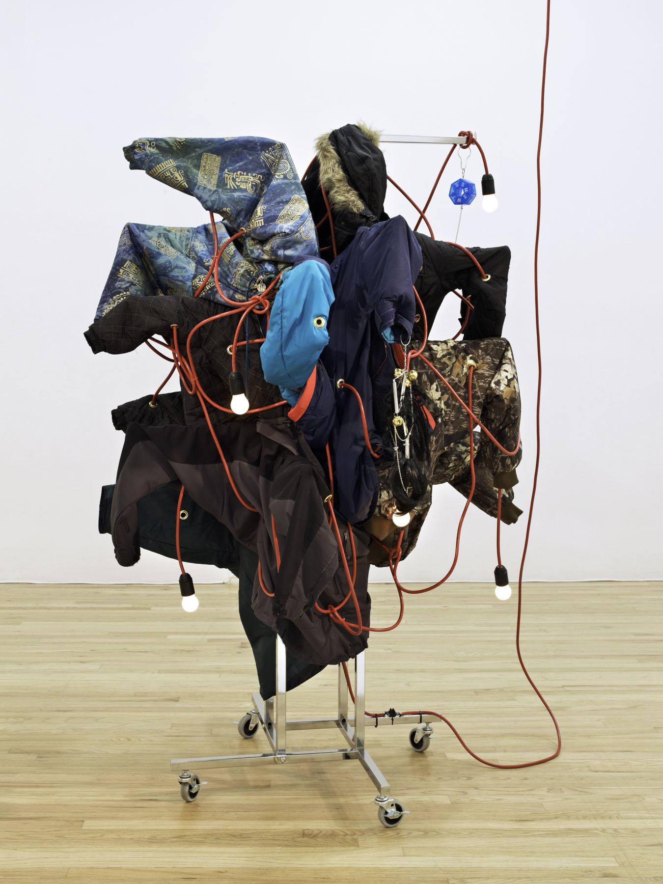 Haegue Yang Wild in Aspen: Wrapping up the Season, 2011 Four-way straight-arm clothing rack (chrome) on casters with nineteen arms, light bulbs (frosted), cable, bells, wigs, pillbox, chain, folder clips, winter coats, and jackets 72 x 36 x 36 inches (182.9 x 91.4 x 91.4 cm) Installation view, The Art and Technique of Folding the Land, curated by Heidi Zuckerman Jacobson, Aspen Art Museum, Aspen, Colorado, 2011