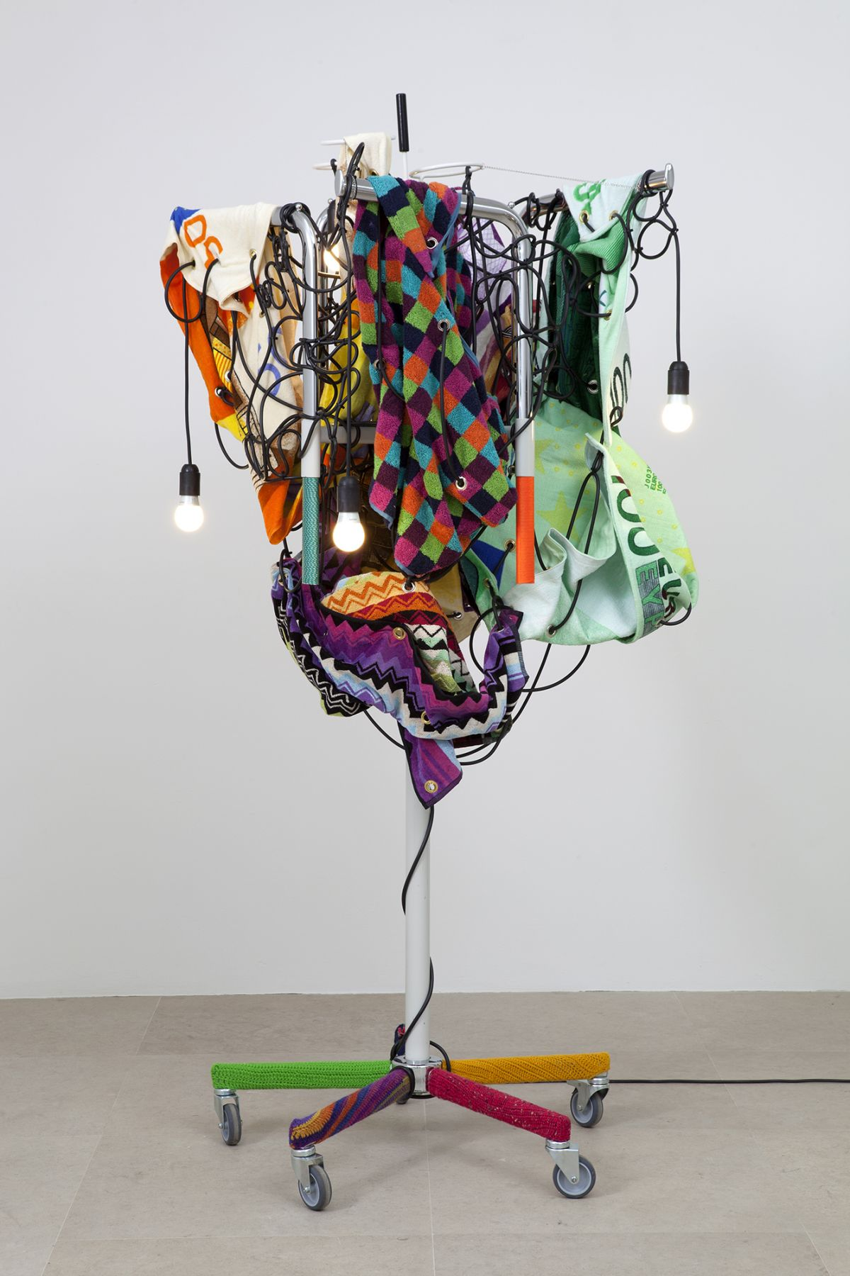 Haegue Yang Towel Light Sculpture - Budget Discipline towards 900 Euro, 2012 Single shaft clothing rack (white, chrome) on casters with 4 arms, light bulbs (frosted), cable, cord, printed towel (Euro and geometric patterns), metal chain, knitting yarn, grommets, umbrella stand 75 5/8 x 34 5/8 x 33 1/2 inches 192 x 88 x 85 cm