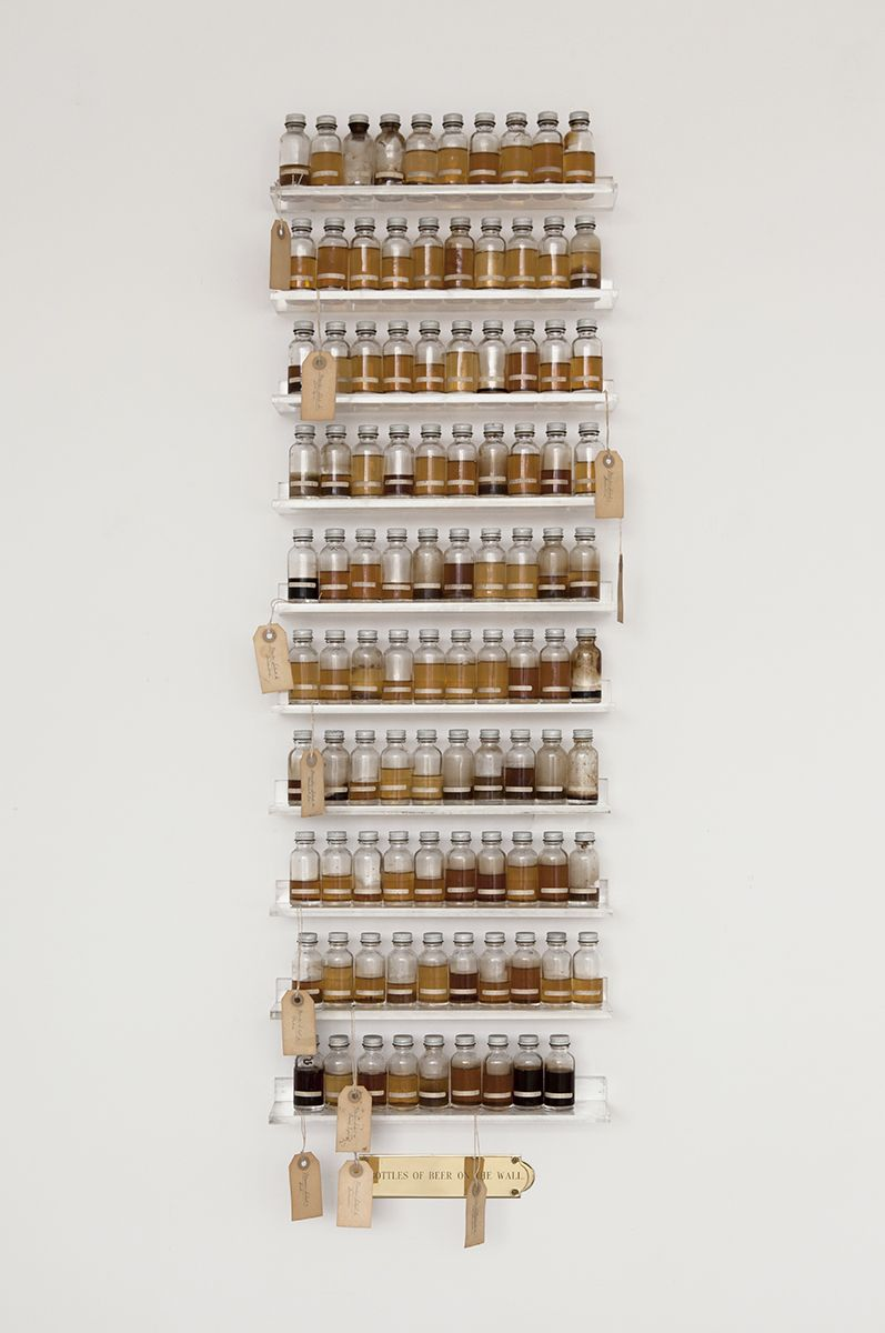 Candy Jernigan, 99 Bottles of Beer on the Wall, c. 1988-89, Beer, glass vials, packing tags, and Plexiglas shelves, 48 x 14 x 3 1/2 inches (121.9 x 35.6 x 8.9 cm)