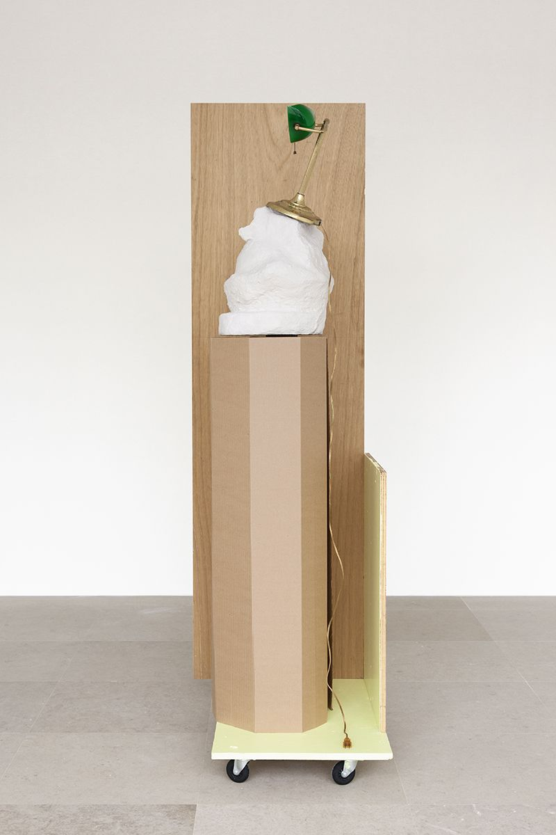 Rachel Harrison,  The Fourth Shade, 200,  Wood, polystyrene, cement, acrylic, cardboard, hollow core door, lamp, wheels, and chromogenic print,  85 x 32 x 24 inches