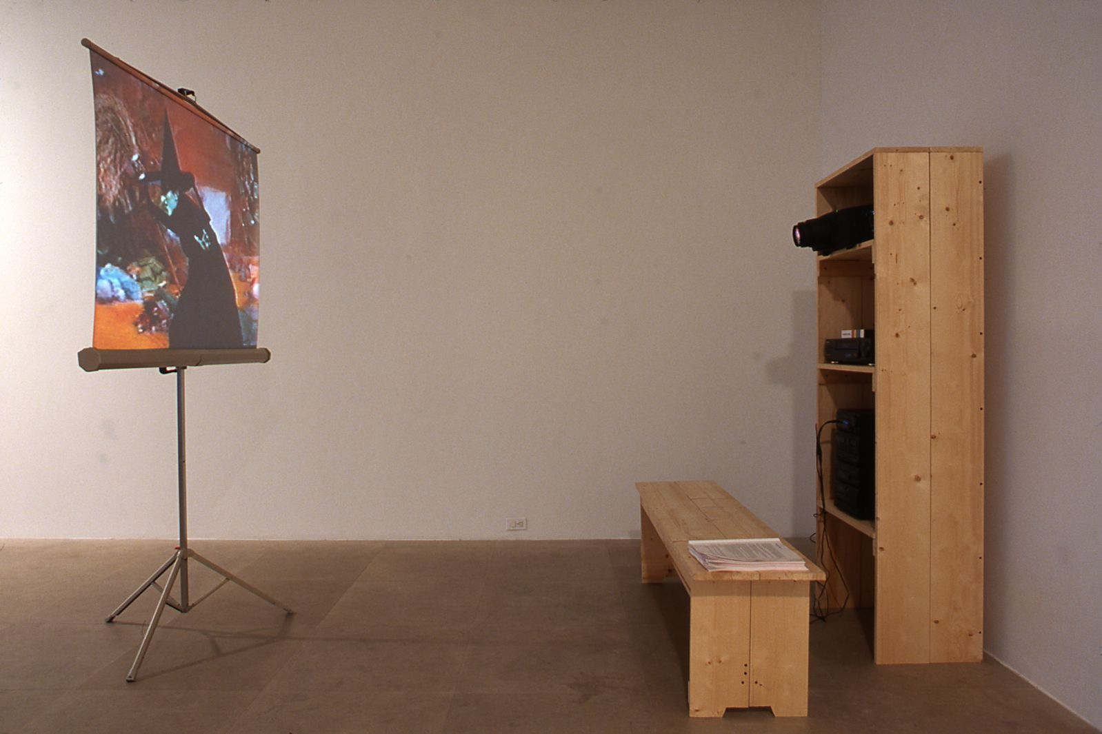 Julie Becker, Suburban Legend, 1999, 1 Beta Master tape, 1 vhs viewing copy, 1 metal homemovie screen, 1 vcr with time clock, 2 headphone sets, wood shelf unit and bench, 3 Suburban Legend manuals