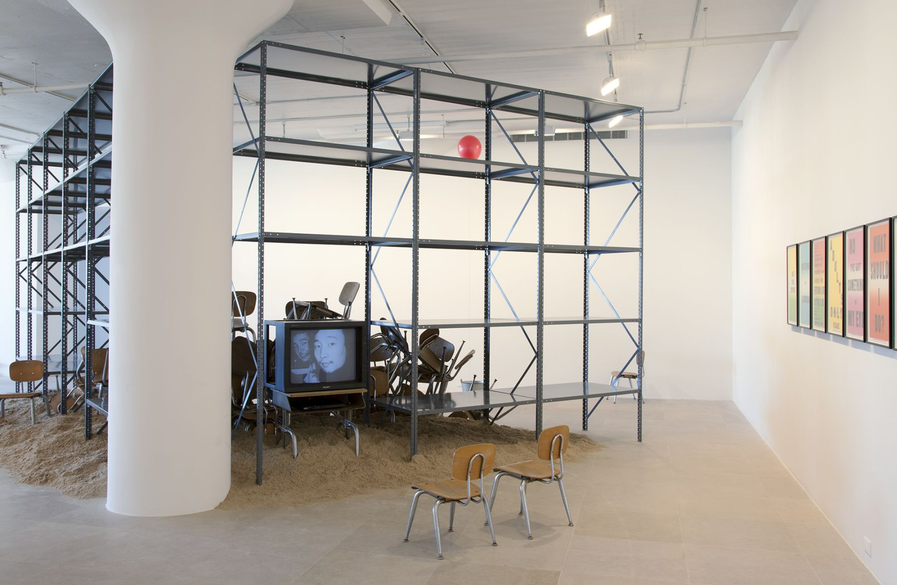 Haim Steinbach, Mothers, Daughters, Children (with '37 Stories About Leaving Home' by Shelly Silver), 1997-2011, metal shelving, sand, wood and metal tables, wood and metal chairs, LCD TV, galvanized bucket, and latex ballon, installation dimensions variable, Installation view, Greene Naftali, New York, 2012