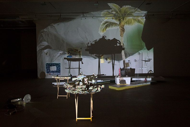 Bag's Circle, 2012, Single-channel video installation with four acrylic-on-canvas paintings, painted foam sculptures, CD rack, plastic cups, sticks, plexiglass, tape, clay, three folding tables, sequined throw, extendable fork, Continuous loop, Dimensions variable
