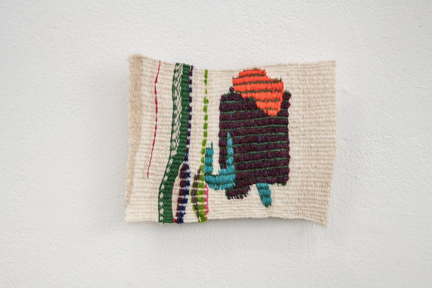 a small weaving with abstracted shapes of colors on a wall