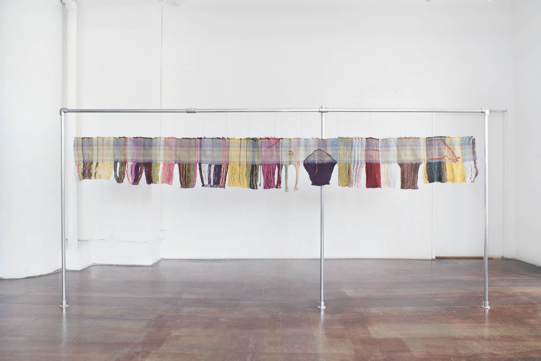 A colorful long weaving hung on a steel bar framing and weighted down on the backside with felted rocks that are attached to the weaving with string