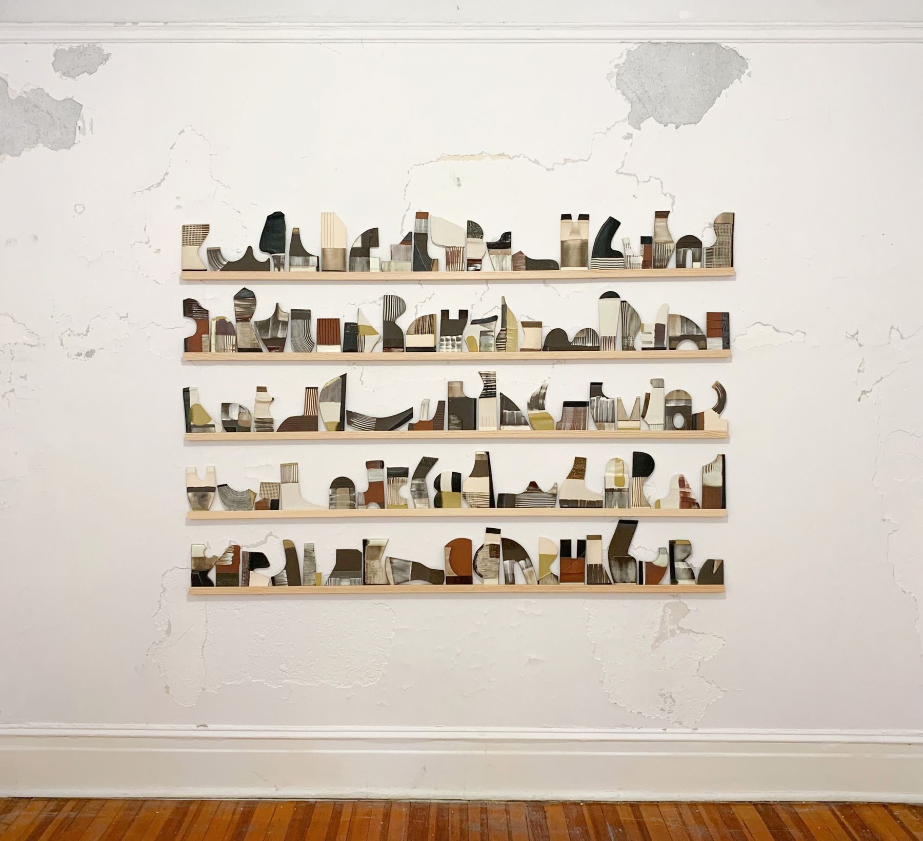 about 100 ceramic tiles made by katy fischer sit on 5 stacked thin wood shelves affixed to an old peeling wall.