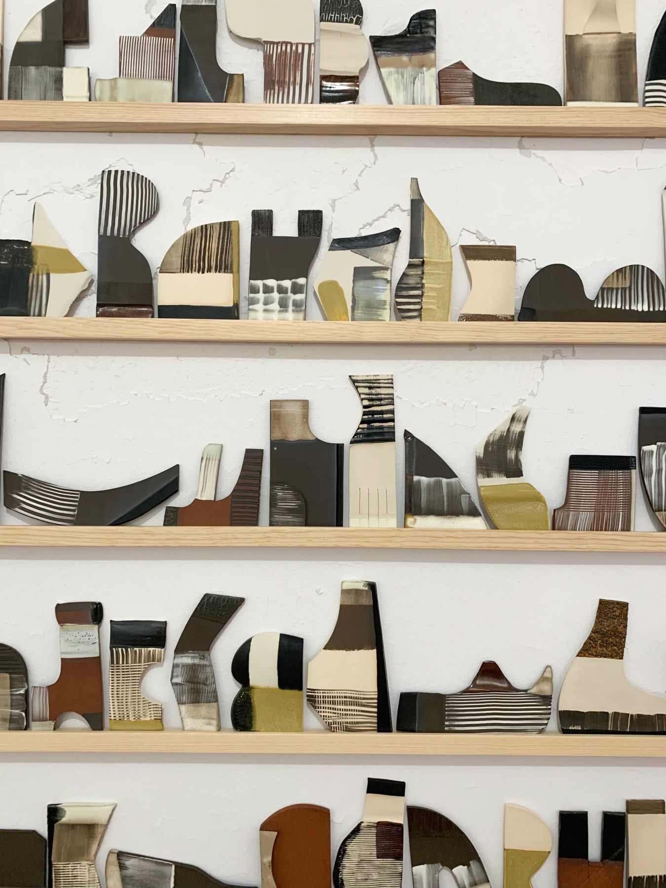 Detail -about 100 ceramic tiles made by katy fischer sit on 5 stacked thin wood shelves affixed to an old peeling wall.